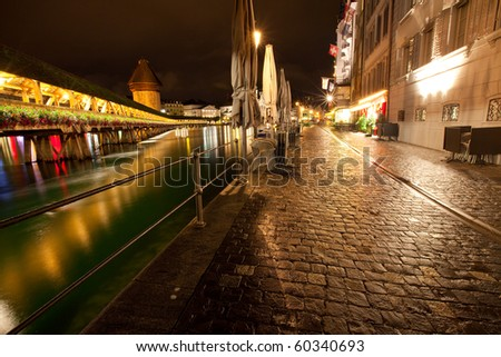 Night time scene of Lucerne water front along the Reuss river with view of the Chapel bridge - stock photo