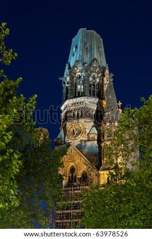 Night time view of illuminated Kaiser-Wilhelm Memorial Church tower in Berlin, Germany - stock photo
