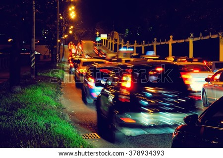 Night traffic jam on a city street: the slow movement of cars with red brake lights in motion blur - stock photo