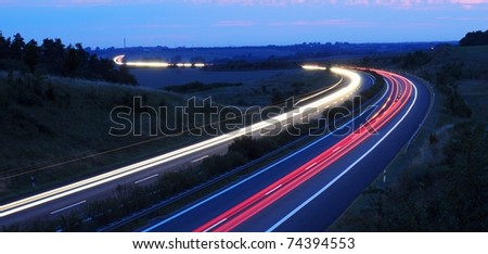 night traffic on busy highway with cars lights and blue sky - stock photo