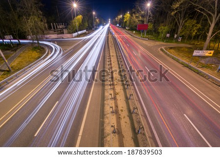 Night traffic on the autobahn with traces from cars - stock photo