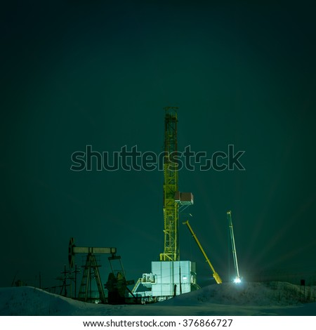 Night view of a derrick drilling and oil pump jack. - stock photo