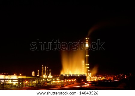 Night view of a petrochemical refinery with chimneys and storage tanks - stock photo