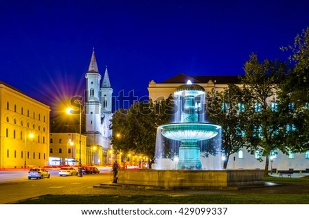 Night view of an illuminated fountain in front of the university in munich with church of saint ludwig at background - stock photo