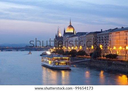 Night view of Budapest with small cruise boat - stock photo