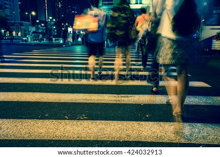 Night view of Crosswalk and pedestrian at modern city zebra crossing street in rainy day. Blur abstract. - stock photo