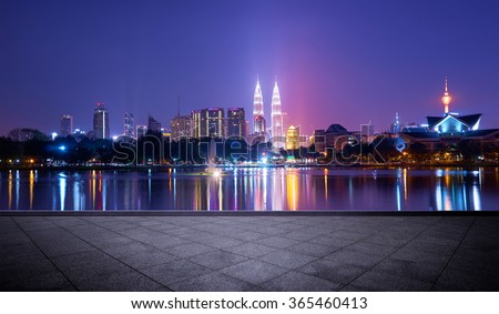 Night view of Kuala Lumpur city with stunning reflection in water and empty concrete square floor - stock photo