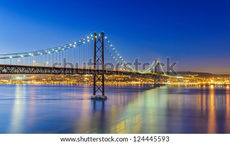 Night view of Lisbon and of the 25 de Abril Bridge, Portugal - stock photo