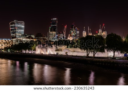night view of London City skyscrapers behind the Tower of London - stock photo