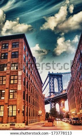 Night view of Manhattan Bridge between Brooklyn Buildings. - stock photo