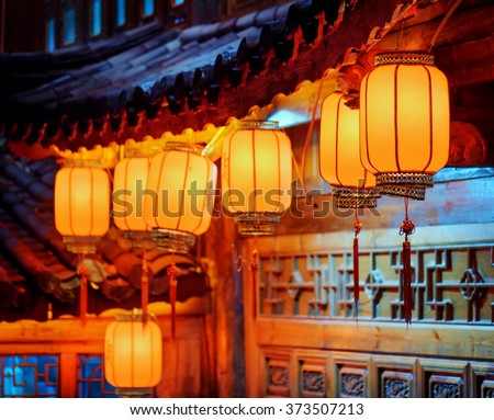 Night view of row of traditional Chinese red street lanterns on carved facade of wooden house in the Old Town of Lijiang, Yunnan province, China. Focus on the first lantern. - stock photo