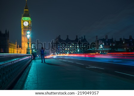 Night view on London landmarks Big Ben Clock and Parliament House on LOndon Bridge over river Thames with light motion blur - stock photo