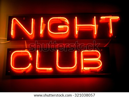 Nightclub neon sign hanging on the wall - stock photo