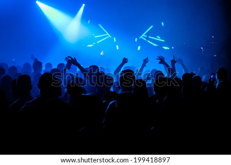 Nightclub party crowd with hands in the air - stock photo