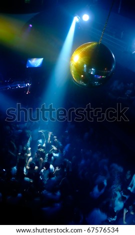 Nightclub scene with disco ball and dance floor crowd in motion - stock photo