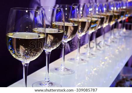 Nightclub wine glasses with white wine lit by party festive lights on dark-purple background, nightlife  - stock photo