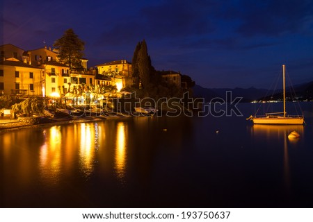 Nightfall overlooking part of the town Varenna on lake Como. Buildings and a sailboat are illuminated by multiple lights reflecting on the water - stock photo
