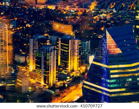 Nightlife and evening illumination, top view on the cityscape. Modern town in night lights - urban background of Istanbul. Night lights on office building and skyscrapers in new city. - stock photo