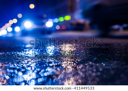 Nights lights of the big city, the night avenue with driving cars. Close up view from the level of asphalt, in blue tones - stock photo