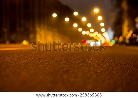 Nights lights of the big city, the night avenue with lanterns, close up view from asphalt level - stock photo