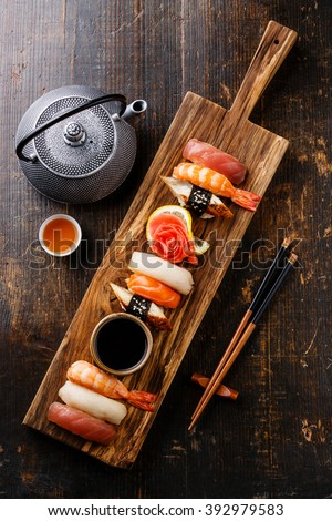 Nigiri Sushi set on wooden serving board and green tea - stock photo