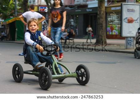 NIKOLAEV, UKRAINE - June 21, 2014: Kid in the play area riding a toy car  - stock photo