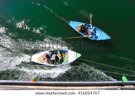 NILE RIVER, EGYPT - FEBRUARY 3, 2016: Men in a row boat tied to the side of a Nile River Cruise ship trying to sell scarves to the passengers in Egypt - stock photo
