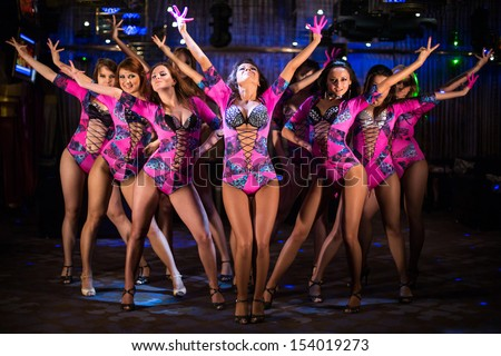 Nine beautiful showgirls in purple costumes with raised hands perform on stage - stock photo