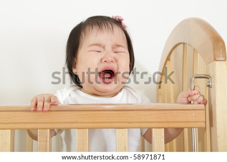 nine month old asian baby infant girl crying and bawling in wooden crib - stock photo