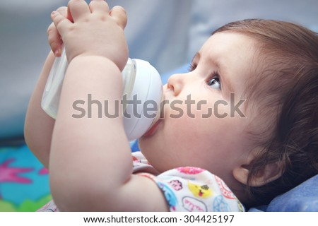 Nine months old baby drinking milk from bottle holding with both hands - stock photo