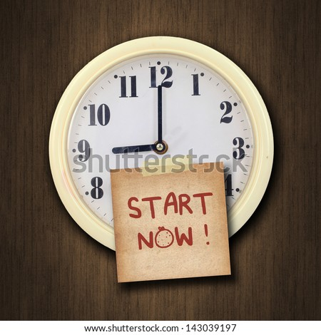 nine o'clock on the wall clock  with the old paper short note and text start now on wood background - stock photo
