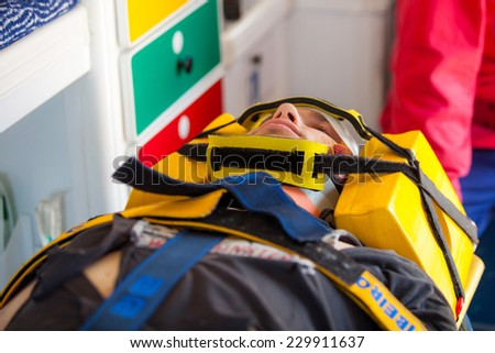 NINE, PORTUGAL - APRIL 12, 2014: Injured man and an emergency worker inside an ambulance at a scene of a train accident simulation in Nine train station - stock photo