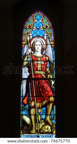 Nineteenth century church window Saint Michael defeating Satan - stock photo