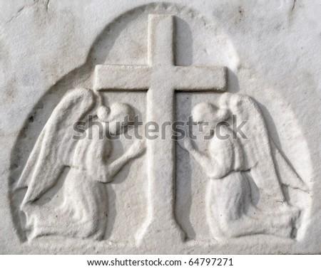 Nineteenth century gravestone detail angels praying at cross - stock photo