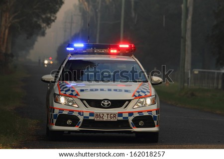 NINGI, AUSTRALIA - NOVEMBER 9 : Police holding cordon in front of bush fire front as it approaches houses November 9, 2013 in Ningi, Australia - stock photo