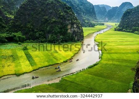 "Ninhbinh, Vietnam, May 17, 2015: Rice field and river ""Ngo Dong"" at TamCoc, Ninhbinh, Vietnam; famous for tourism at Vietnam. Ninhbinh city is located in the south than the capital Hanoi, Vietnam. - stock photo"
