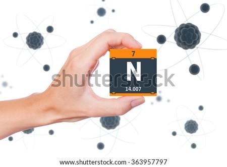 Nitrogen element symbol handheld and atoms floating in background - stock photo