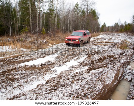 NIZHNY TAGIL. RUSSIA - JUNE 12, 2013: Broken logging road in the heart of Siberia. Red offroad car overcomes winter thaw - stock photo
