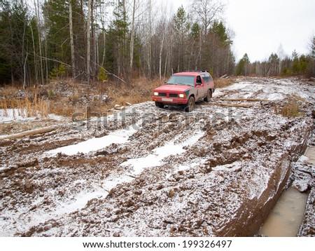 NIZHNY TAGIL. RUSSIA - JUNE 12, 2013: Broken logging road in the heart of Siberia. Red offroad car overcomes winter thaw - stock photo