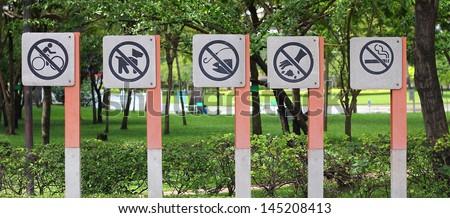 No bike riding, No dogs, No Fishing, No Littering and No Smoking sign in a garden - stock photo