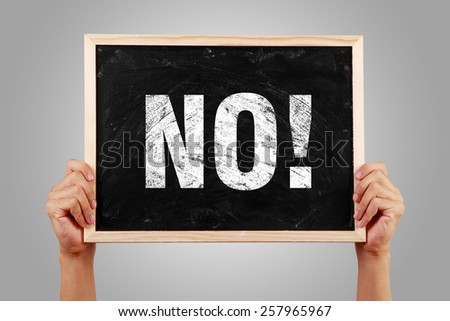 No blackboard is holden by hands with gray background. - stock photo