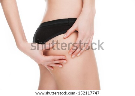 No cellulite. Close-up of woman in black panties touching her buttocks while isolated on white - stock photo