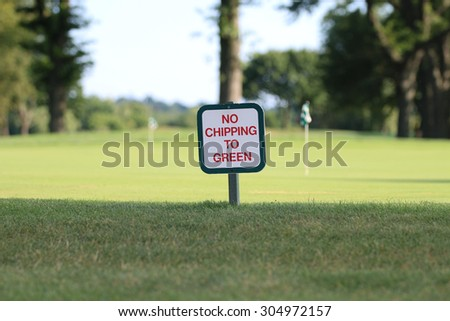No Chipping to Green Golf Course Sign Positioned near Green, with A Putting Green and Trees in the Background. - stock photo