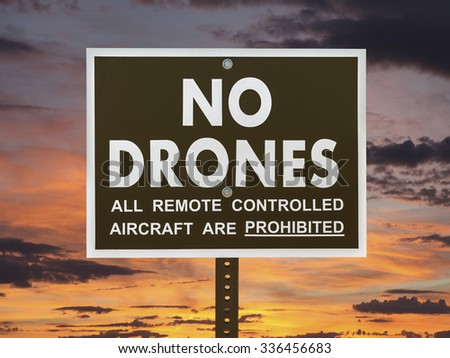 No drones sign with sunset sky. - stock photo