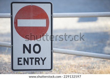 No entry sign on boom gate to restricted area of property in blurred background, with copy space. - stock photo
