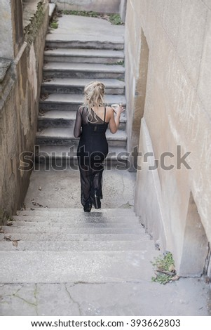 no face. Back view. Full length Portrait of Beautiful caucasian woman go on concrete old retro abandoned ladder along fence in perspective Cute girl hold black tea cup. Wear sexy long dress - stock photo