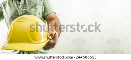 No face Unrecognizable person construction worker man holding in hands yellow helmet on green texture wall with wallpaper background Empty copy space for inscription Man wear stripped shirt  - stock photo