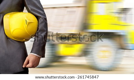 No face Unrecognizable person engineer construction worker hold in hand yellow plastic helmet for workers security against large big truck with load on road Idea concept of logistic transportation - stock photo