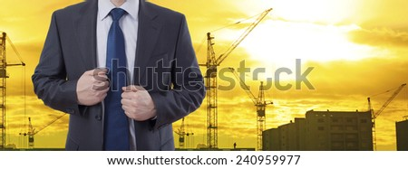 No face Unrecognizable person man engineer keep flaps of his jacket on background of new highrise apartment buildings and construction cranes of evening sunset cloudy sky Silhouette Crane lifts load - stock photo