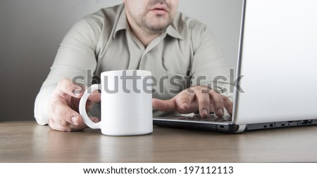 No face Unrecognizable person of business man using gray silver laptop with a white cup of coffee Businessman working on wooden natural table  - stock photo